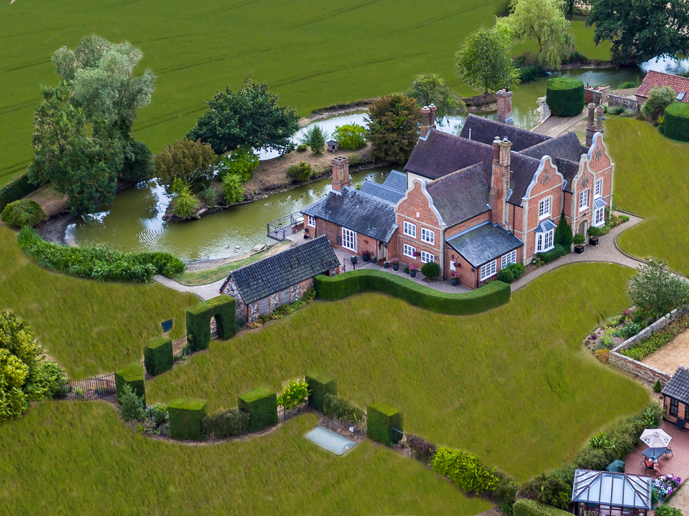 An Aerial photograph of a large house and gardens in the Suffolk countryside